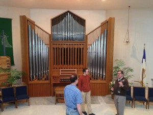 Pastor in conversation in front of the relocated organ.